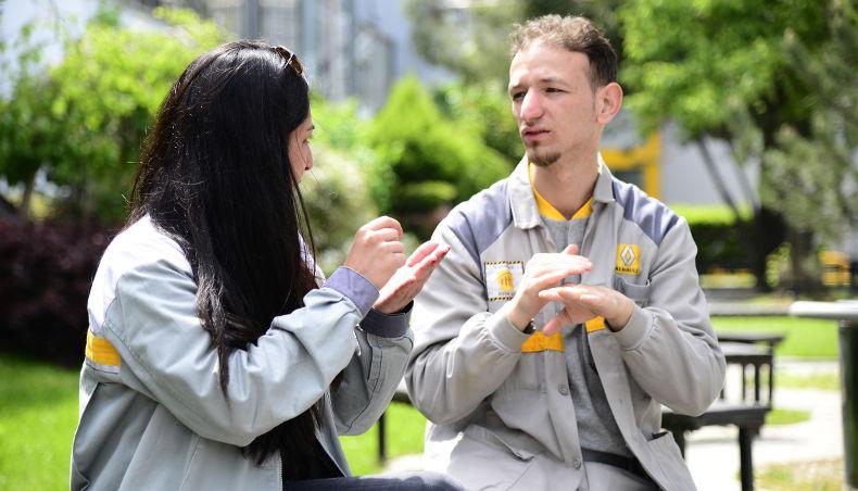 Le Groupe Renault favorise l'inclusion des personnes avec un handicap - deux employés pratiquent la langue des signes