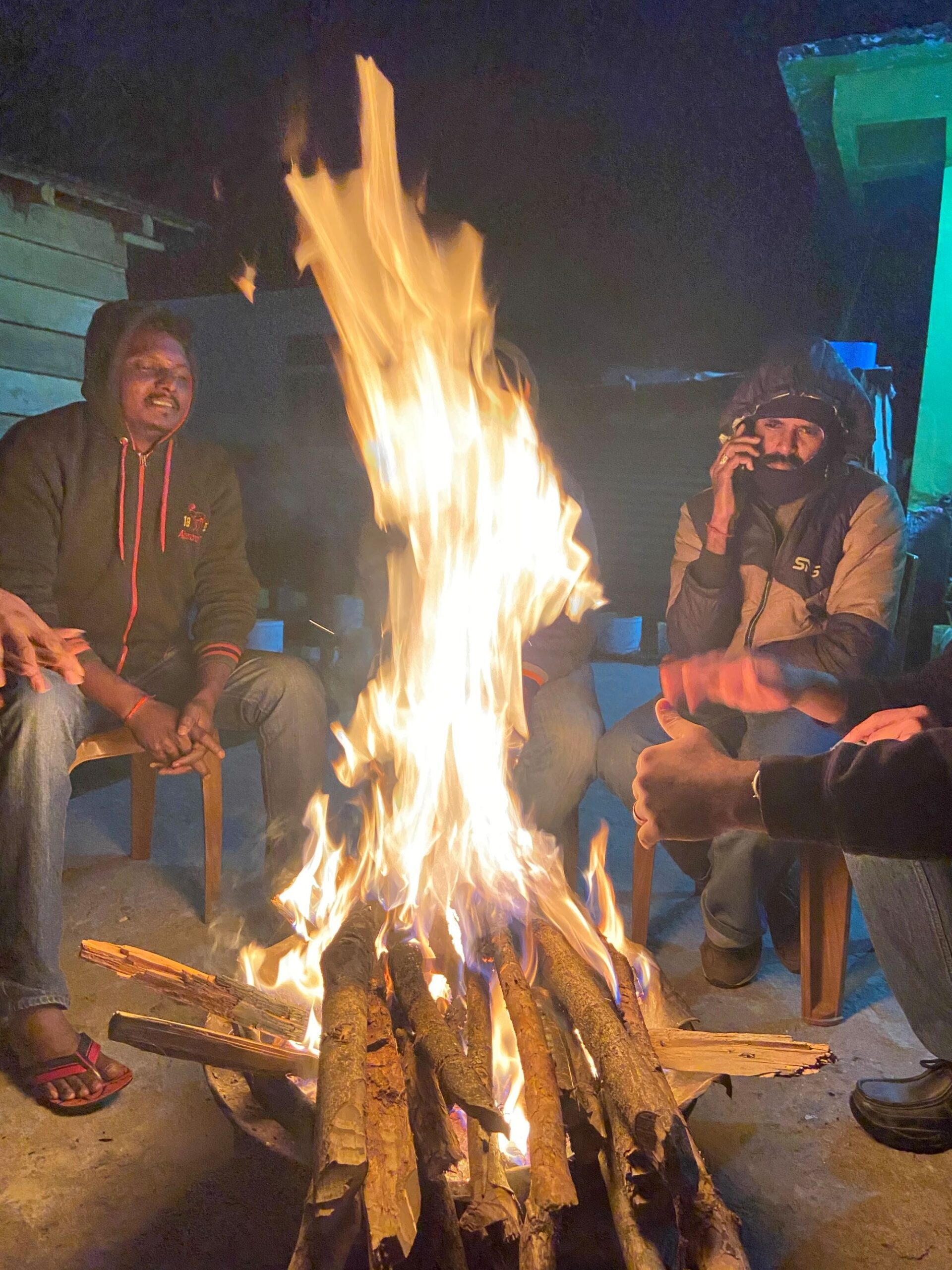 The members of the expedition warm up around a campfire